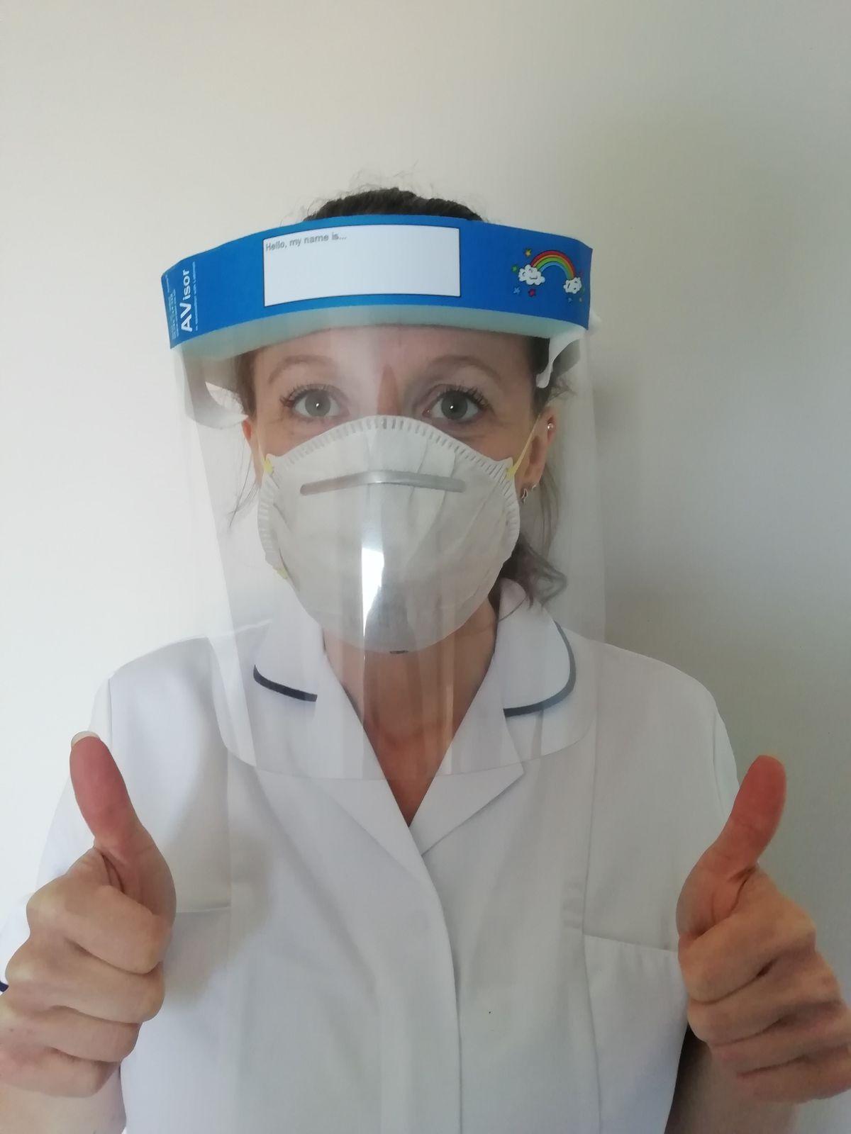 A health worker wears a visor
