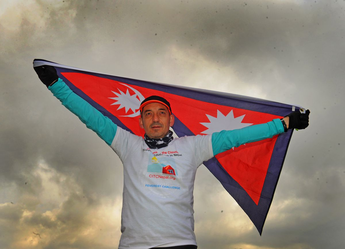 Raising money for Classrooms in the Clouds, running the height of Everest everyday throughout February, holding the flag of Nepal, Shayne Adams, at Ludlow