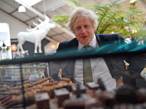 Prime Minister Boris Johnson looks at a display of cakes and desserts as he talks with business owners during a visit to Lemon Street Market in Truro, Cornwall to see how they are preparing to reopen ahead of Step 2 of the road map (Justin Tallis/PA)