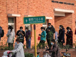 Residents line up to receive booster shots against Covid-19 at a vaccination site in Beijing