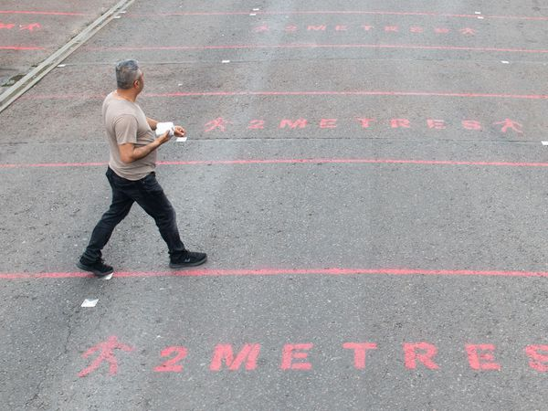 People walk over two metre social distancing markings