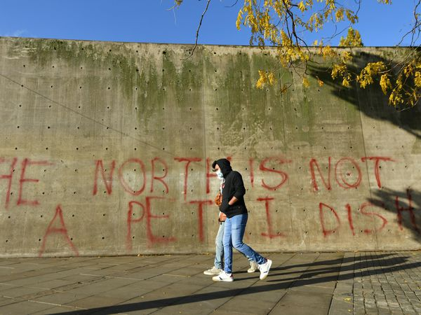 People walk past graffiti