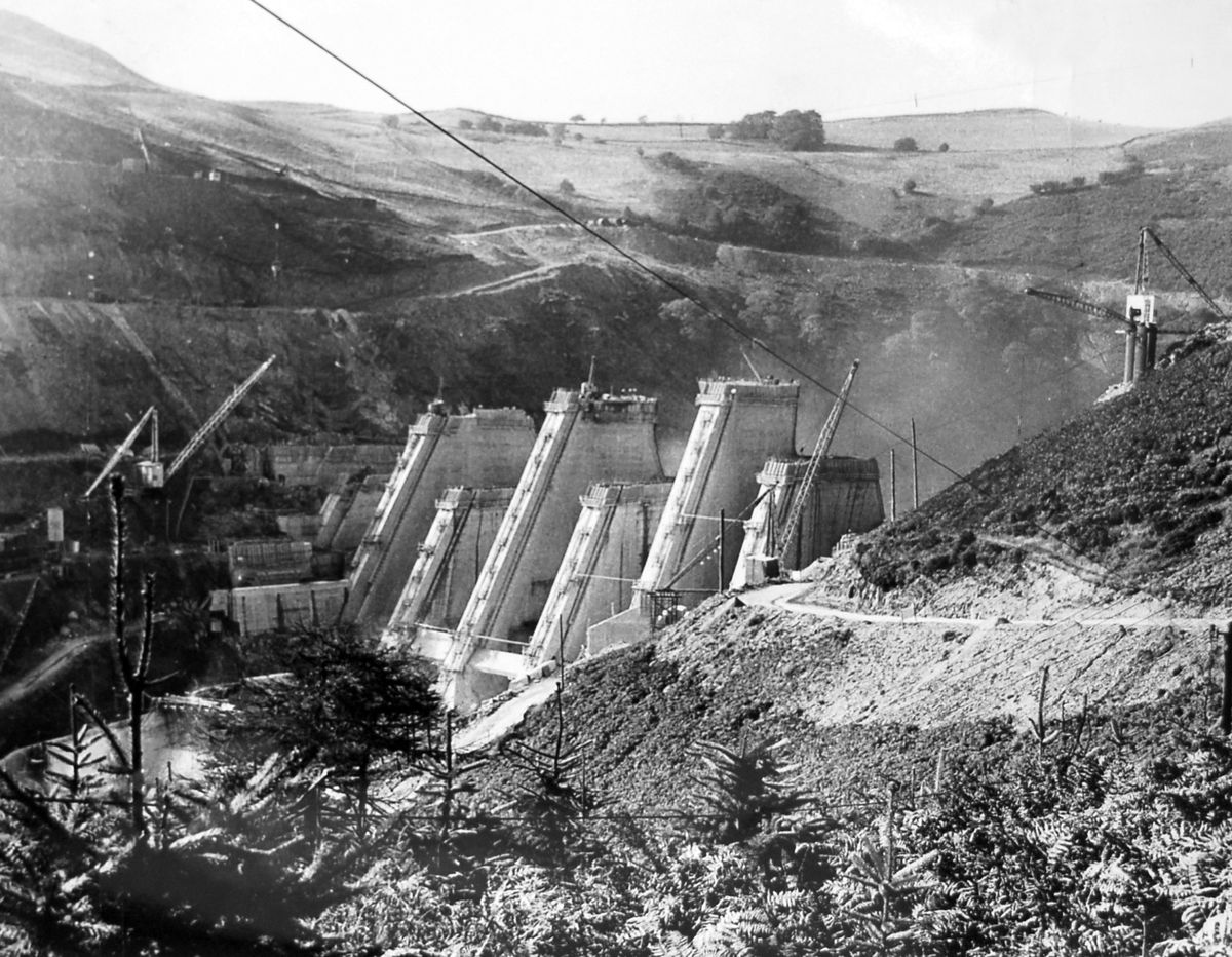 """The massive dam at the Clywedog reservoir in Mid Wales takes shape in September 1966. """"The most advanced of the buttresses now stands 200 feet above the stream. Eventually the crest of the dam will be topped out at 237ft, about level with the crane on the right,"""" said the original caption."""