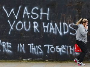 A woman walks past graffiti calling on people to wash their hands during the Covid-19 crisis in East Belfast.  PA Photo. Picture date: Thursday April 2, 2020. See PA story HEALTH Coronavirus Ulster. Photo credit should read: Niall Carson/PA Wire.