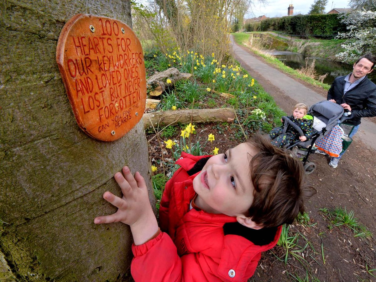 Stephen Brazier is pictured with Eric Brazier-Cooke, aged four, and Elliott Brazier-Cooke, one, admiring one of the wooden hearts