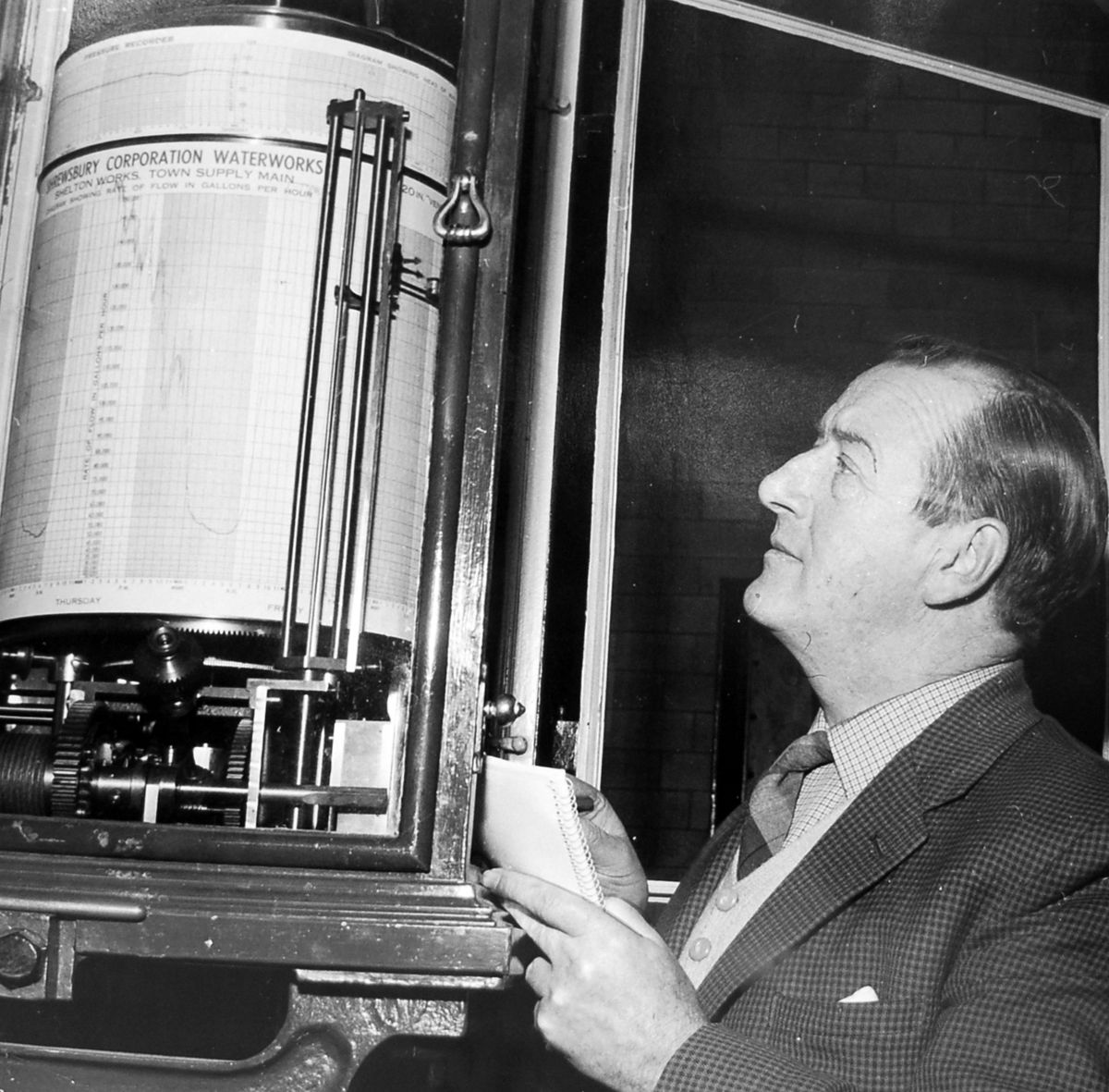 """The horrifying readout from this 20-inch Venturi meter showed that 500,000 gallons of water were running to waste each day in Shrewsbury as a result of burst mains and pipes throughout the town. Taking a note of consumption figures in January 1962 was Mr B Egan, assistant water engineer at Shrewsbury. """"It is to be hoped that in a few days the reading might well be back to normal,"""" said the original caption."""