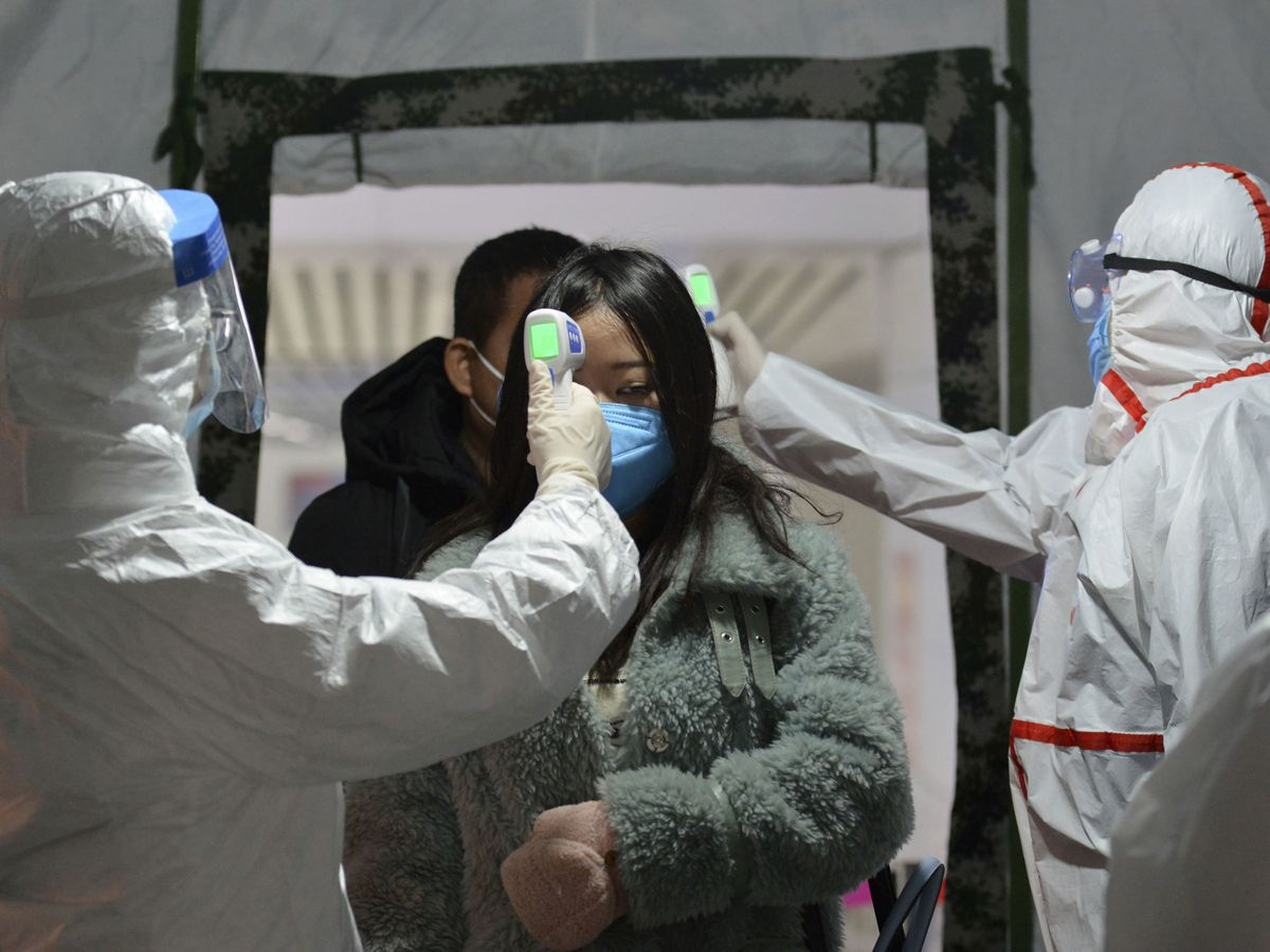People given temperature checks from health officials amid the coronavirus outbreak in Wuhan, China
