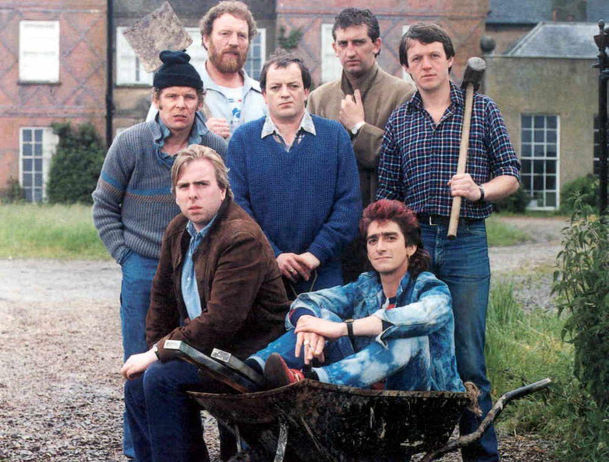 Gary Holton (as Wayne, in wheelbarrow) with his Auf Wiedersehen Pet co-stars.