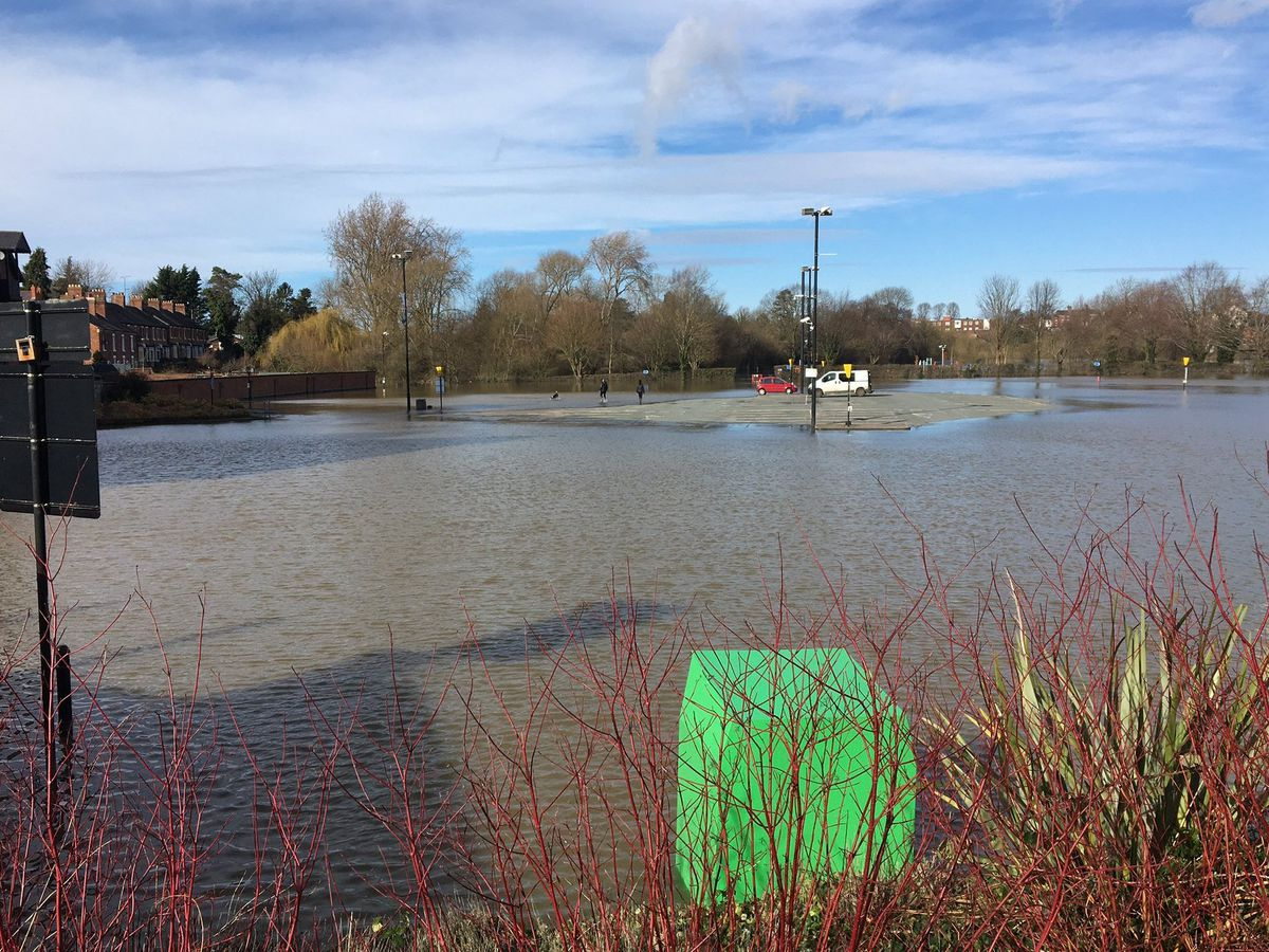 A car and van face being cut off as flood waters rise on the Frankwell car park in Shrewsbury