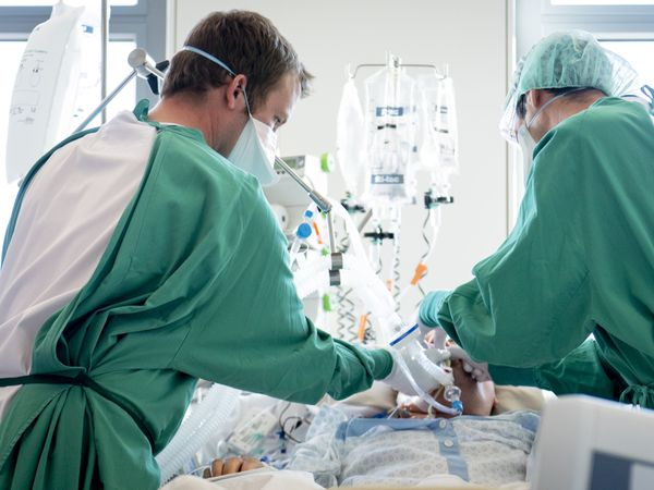 Swiss army soldier Julien, right, helps a medical worker to treat a patient infected with the coronavirus and ill with with COVID-19 in the intensive care unit at the HiB Hospital (Hopital intercantonal de la Broye) in Payerne, Switzerland, Monday, April 6, 2020. Countries around the world are taking increased measures to stem the widespread of the SARS-CoV-2 coronavirus which causes the Covid-19 disease. For most people, the new coronavirus causes only mild or moderate symptoms, such as fever and cough. For some, especially older adults and people with existing health problems, it can cause more severe illness, including pneumonia.(Laurent Gillieron/Pool/Keystone via AP).