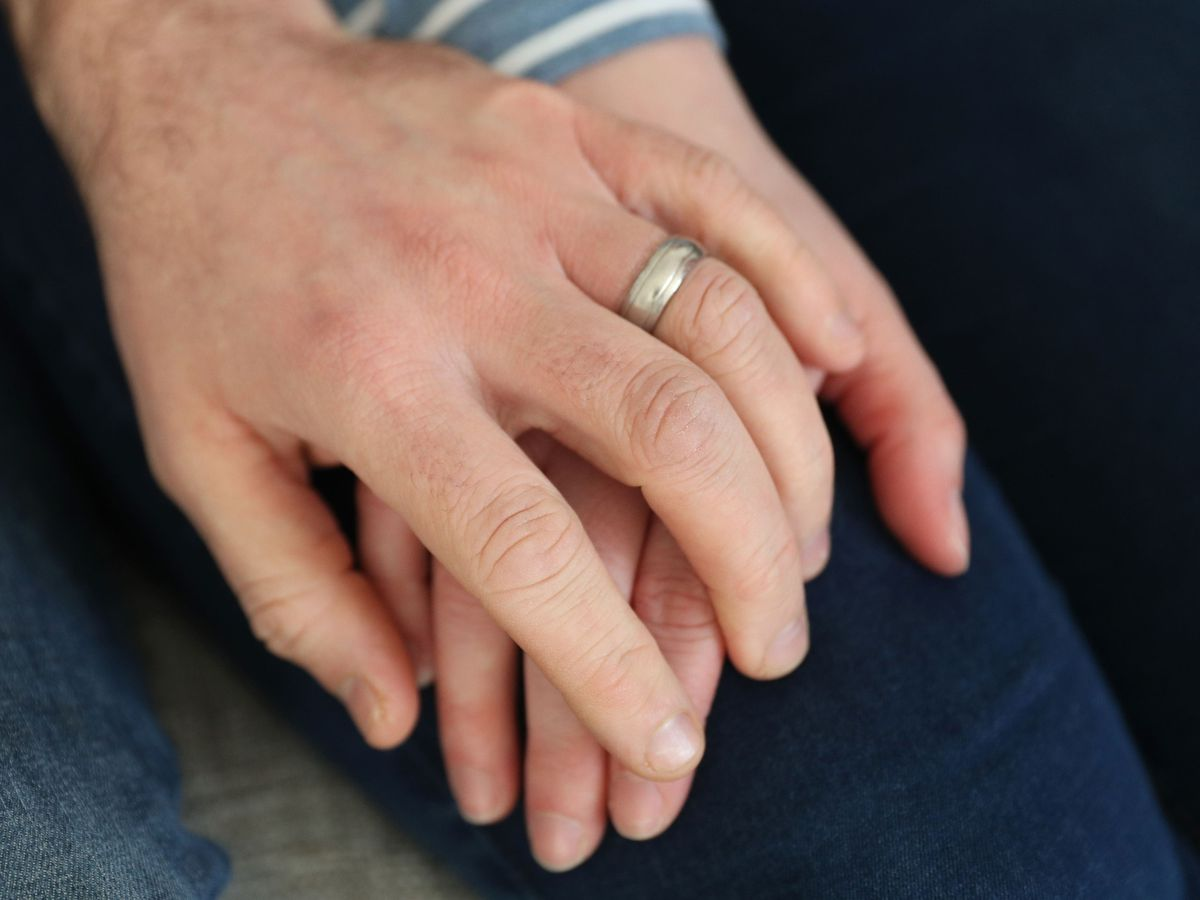 A married couple hold hands.