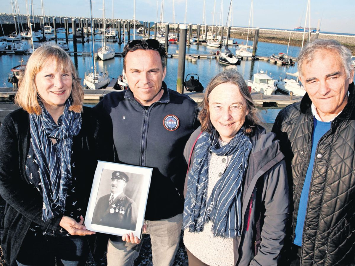 Bri's grandchildren travelled to a lifeboat station in Holland to give thanks for saving his life 100 years ago. From left are Clare Soltysiak, her sister Sally Moss, and their brother Richard Dodwell with, second from left, Bart Gorthmanns, the great-grandson of Bri's rescuer, whose photograph he is holding.