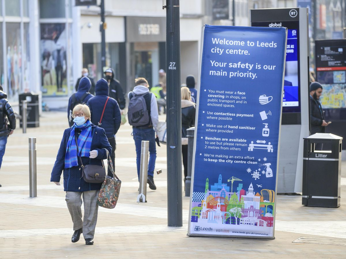 People walk past a Covid information poster in Leeds