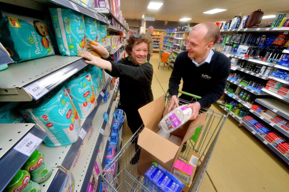 Harry Delves and Jackie Emberton refill shelves at Tuffins in Craven Arms