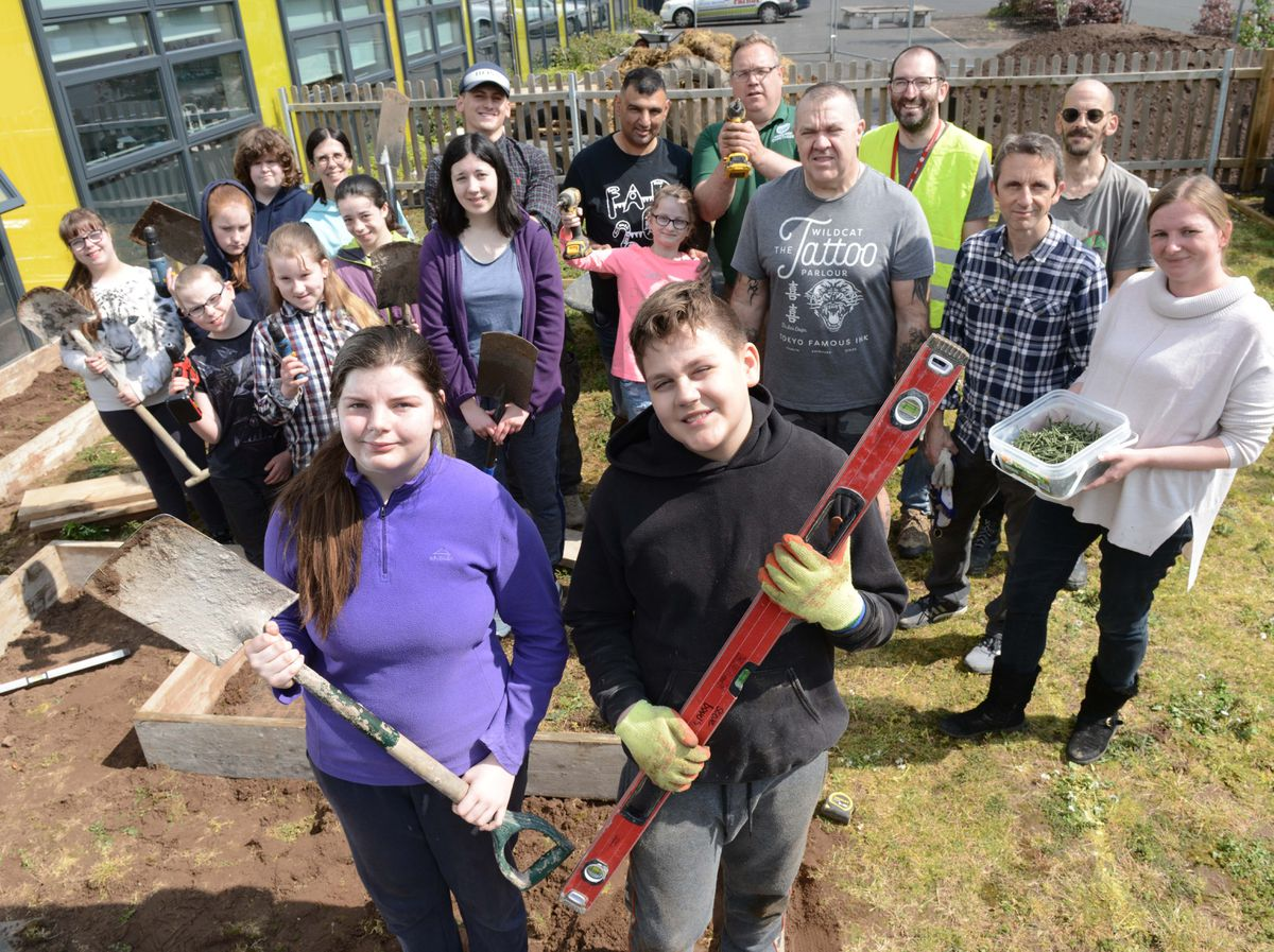 Emily Chapel, 14, and Jack Cooper, 17, with staff and volunteers creating the outdoor classroom at Telford Priory School
