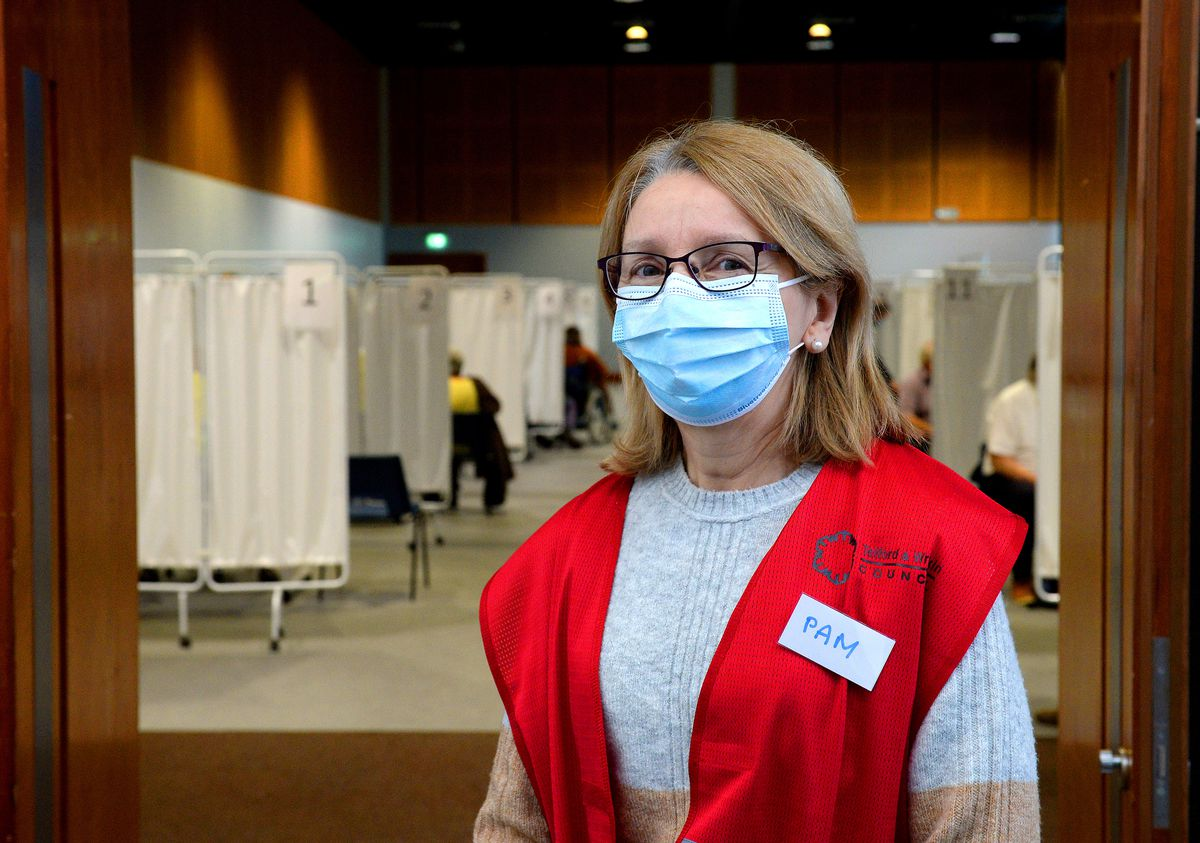 Volunteer Pam McPhillips helps to direct patients into the bays to get their jabs at Telford International Centre