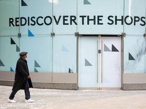 A man wearing a face mask walks past an empty shop unit