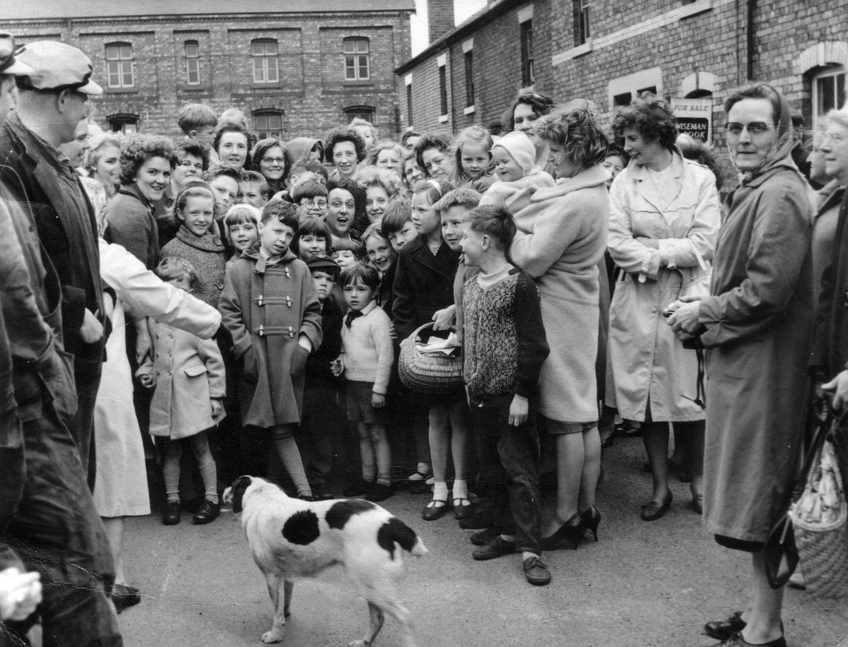 """Comedian Ken Dodd received a tumultuous reception when he went to Spa Street in Shrewsbury while appearing at the Granada in the town in May 1964. He left his Jag behind and was driven in a Mini to the area known as the """"Back o' the Sheds"""" by the Shrewsbury Chronicle photographer, allegedly on a hunt for jam butties. The picture actually used by the paper showed Ken sharing a giant jam buttie with Shrewsbury's Domino Queen, Miss Margaret McCarthy of number 5. We're pretty sure she is the young blonde woman immediately to the right of Doddy as you look at the picture (and Margaret, if you're out there, we'd love to hear from you). Ken knew Shrewsbury quite well, having attended Priory School as an evacuee from Liverpool."""