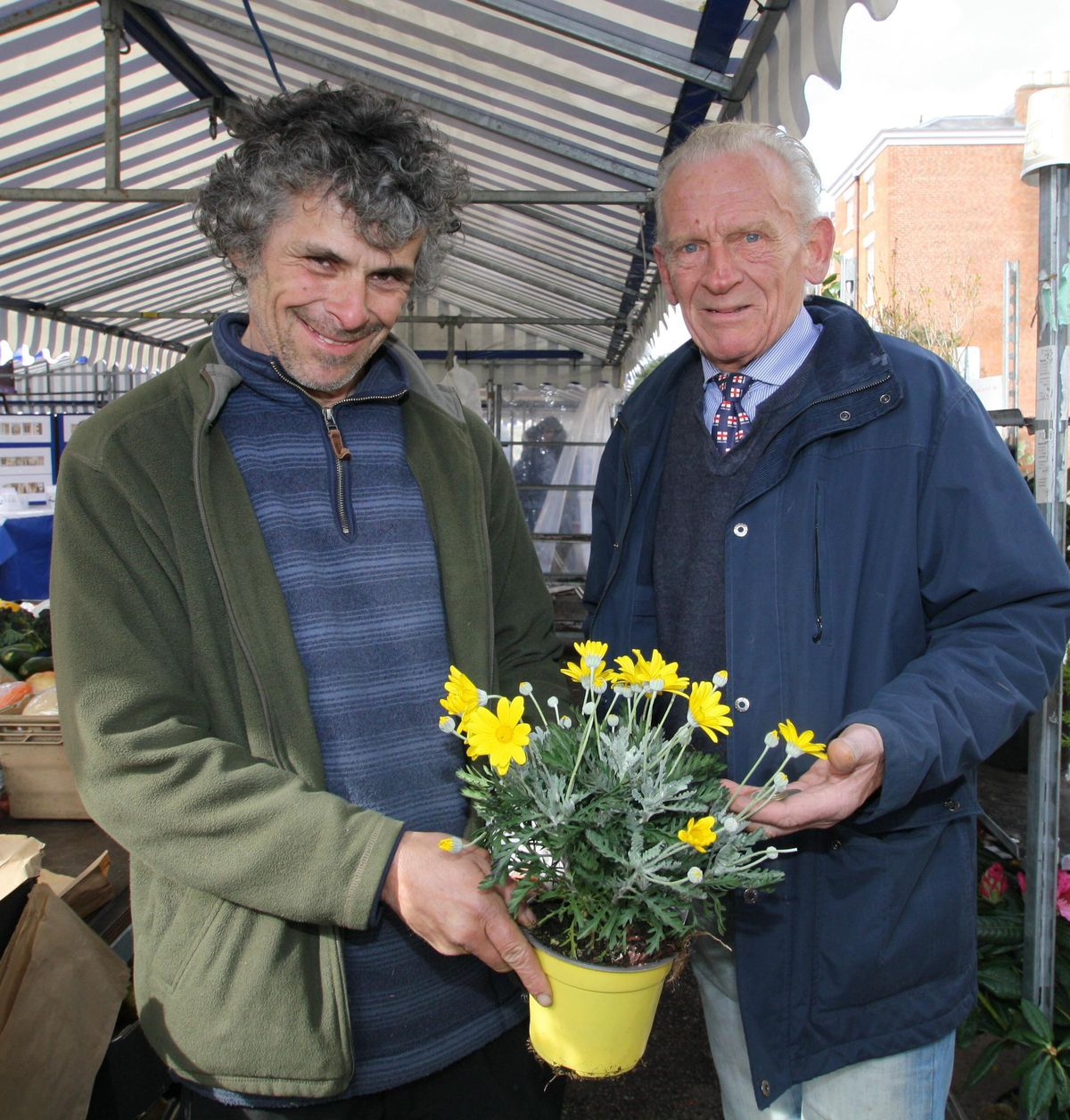 Roger Farmer, left, makes a sale to Kenneth Clinton on his fruit, vegetable and flower stall.