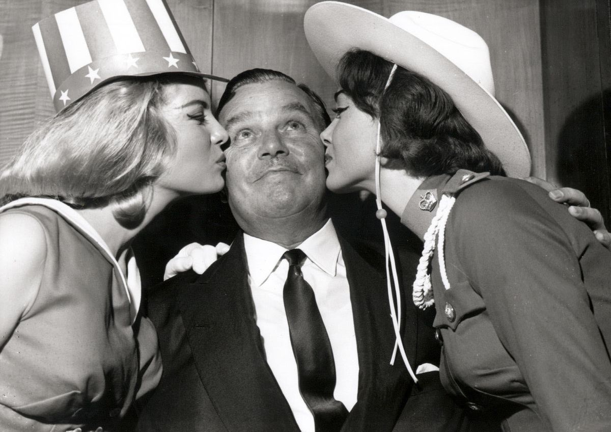 Holiday Camp 'King' Billy Butlin receiving a dual kiss from two Miss World contestants