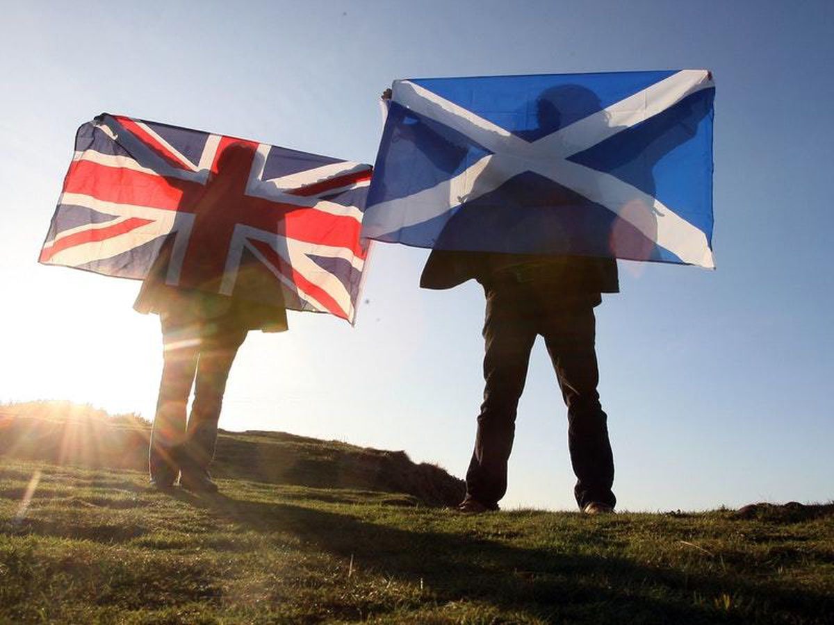 Scottish and UK flags held up