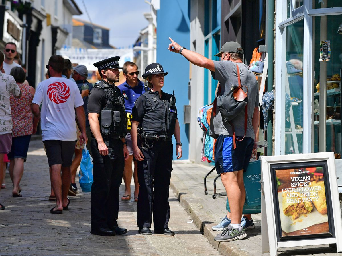 Police officers speak to a member of the public in St Ives