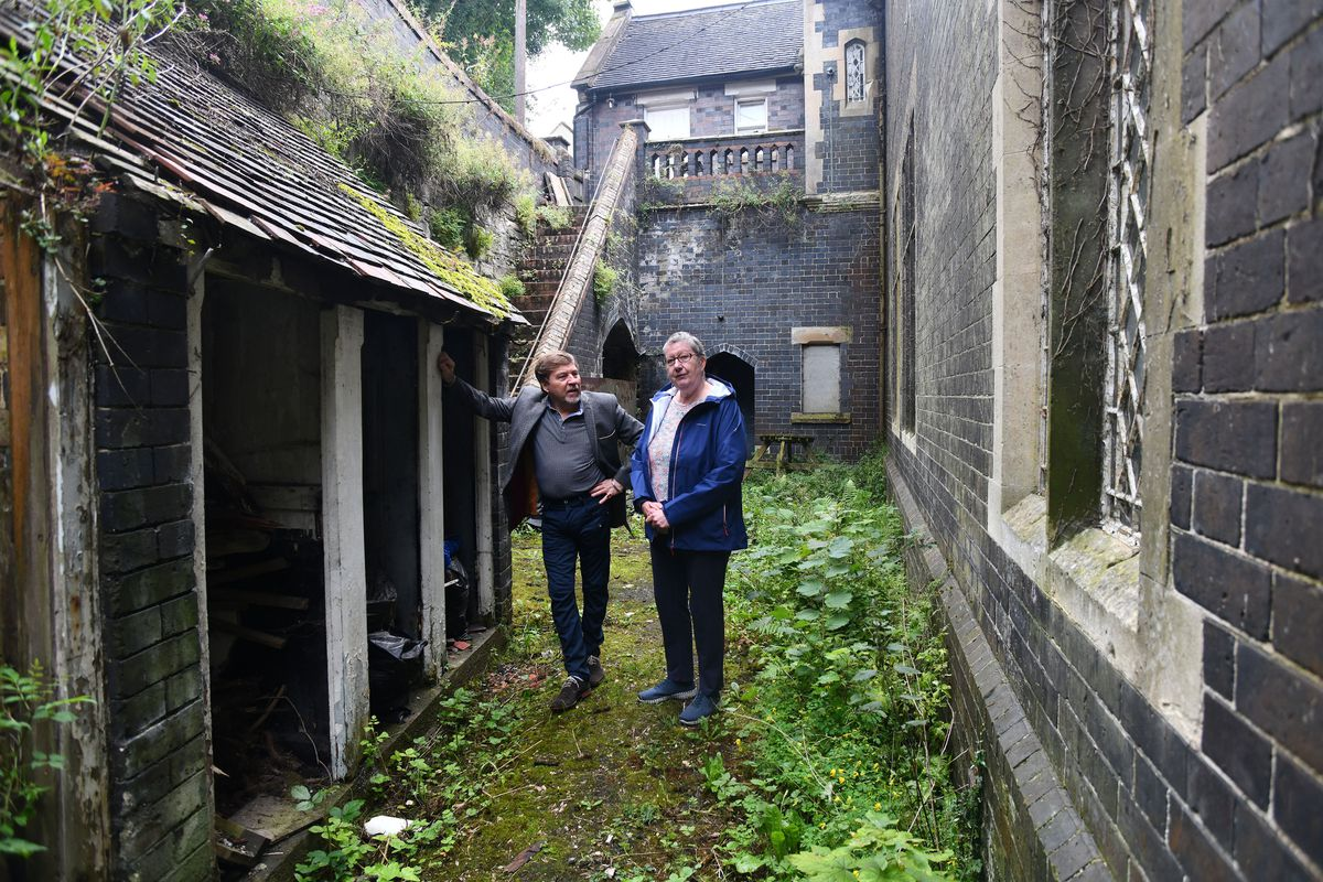 It's different for girls... Wayne Owen and Jean Wright at the girls' outside toilets. Boys had a long trek down steps almost as far as the Parish Rooms on Madeley Hill. Picture: Dave Bagnall.