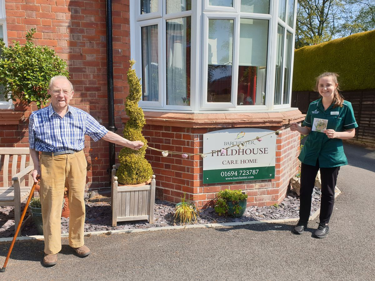 Field House resident John Clark and care assistant Tesni Merrett with the hand-knitted donated bunting