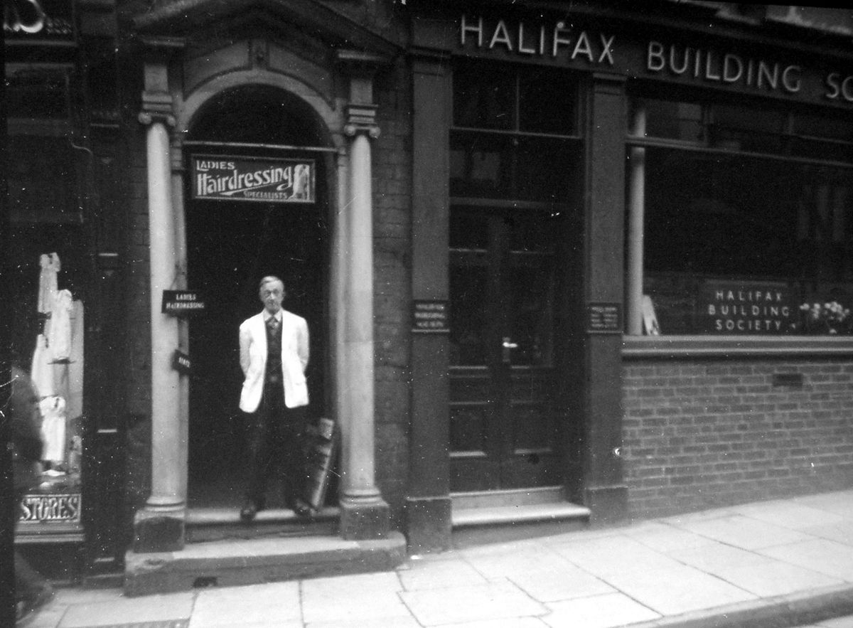 """Wilfred Moore outside Moore's hairdressers at 3a High Street, Shrewsbury. He was a ladies' hairdressing specialist, according to the sign above him. The date of  January 1951 is on the back of the picture, which was originally loaned to us by his daughter Mrs Sybil Waite, who told us at the time: """"We lived above the shop my grandfather had which sold out to Scottish wool and hosiery stores. You can just see it next door."""""""