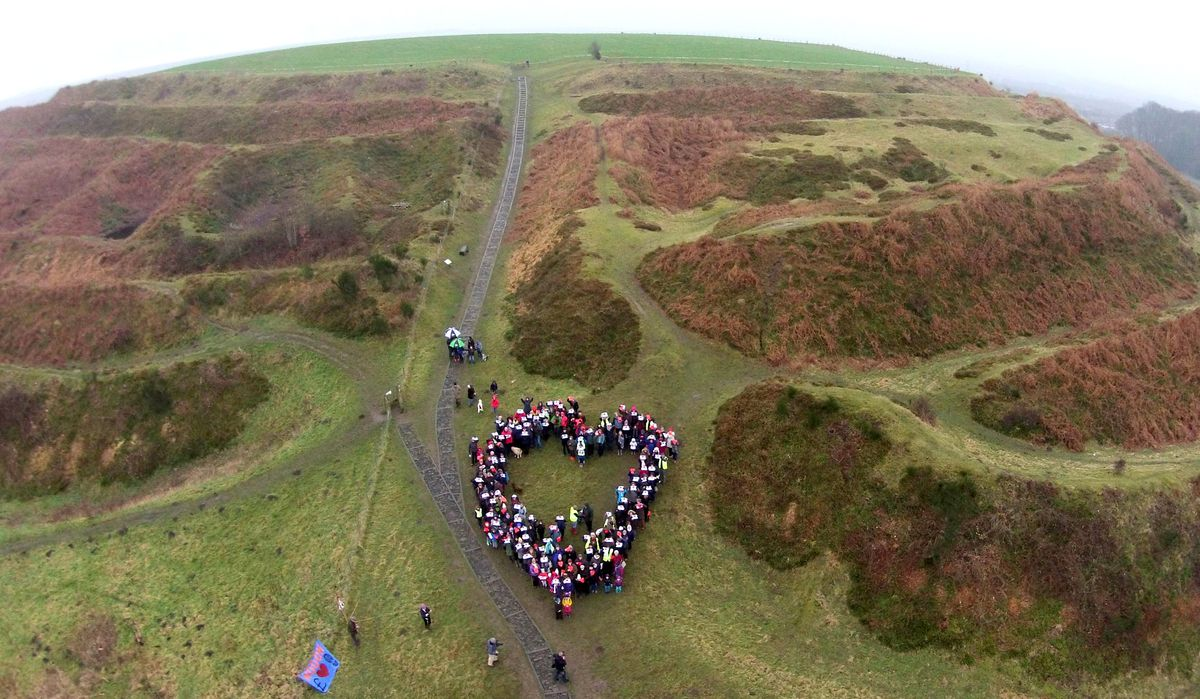People form a heart at a Hillfort Hug organised by campaign group, HOOOH
