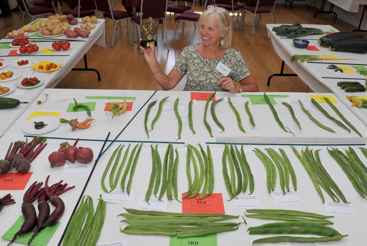 Sandy Burton, chair of the South West Shropshire Gardeners Club, at Lydbury Village Hall, with some of the winning produce on display.