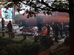 Hospital staff prepare to evacuate patients on stretchers (Ali Greef/AP)