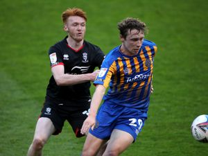 """Shrewsbury Town's Matthew Pennington (right) and  Lincoln City's Callum Morton battle for the ball during the Sky Bet League One match at Montgomery Waters Meadow, Shrewsbury. Picture date: Tuesday April 27, 2021. PA Photo. See PA story SOCCER Shrewsbury. Photo credit should read: Nick Potts/PA Wire...RESTRICTIONS: EDITORIAL USE ONLY No use with unauthorised audio, video, data, fixture lists, club/league logos or """"live"""" services. Online in-match use limited to 120 images, no video emulation. No use in betting, games or single club/league/player publications.."""