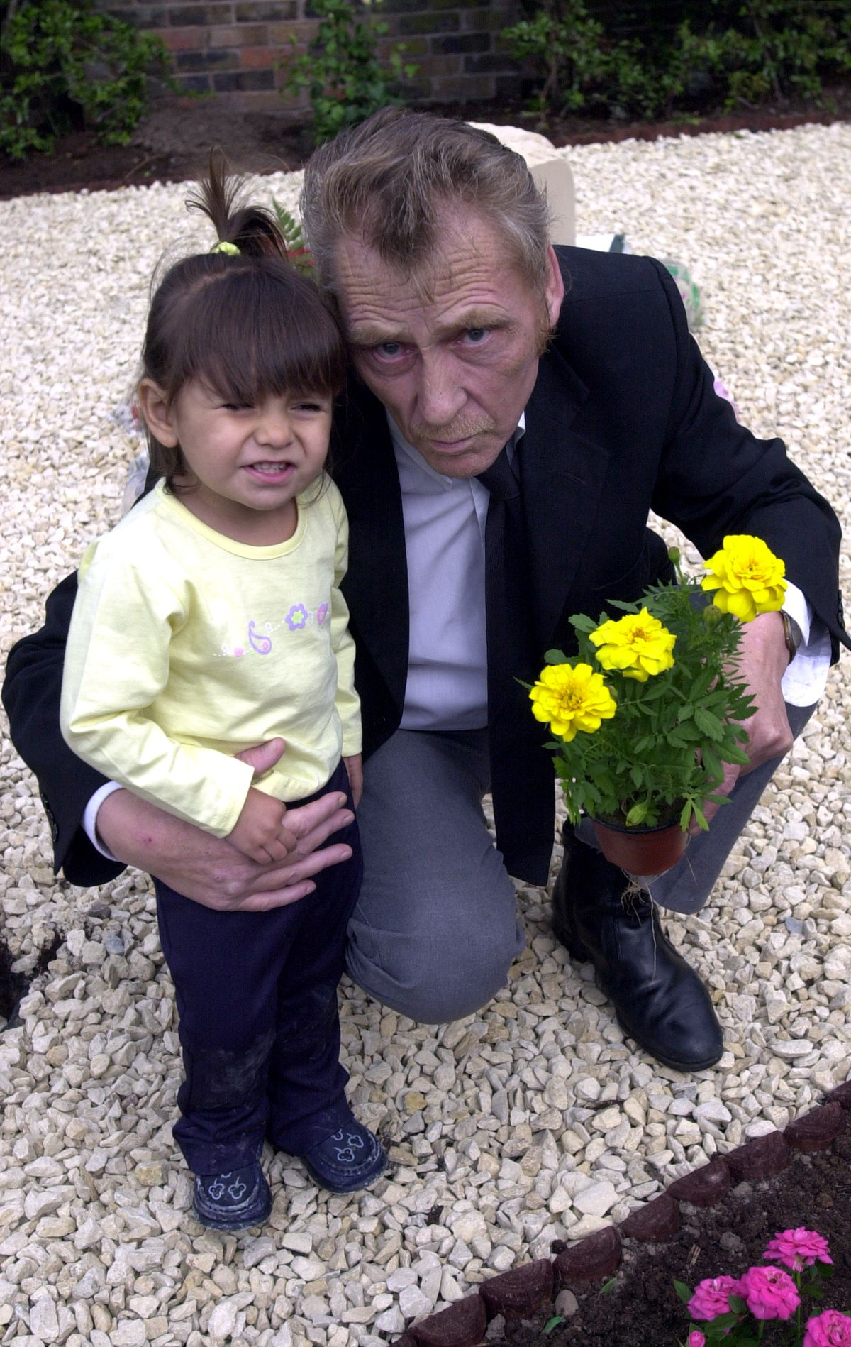 George Lowe with grandchild Tasnim at the family memorial garden in Leegomery