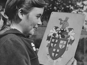 "Here's a question for Dawley folk – do you know your town coat of arms, and the town motto? Well, here they are in a May 1959 picture from our files, when the coat of arms was quite new. As you can see the Latin motto is Trinis Catenis Vinctus which according to Google translate means ""on three chains."" The young lady is not named, unfortunately. According to a heraldry website ""the arms were officially granted on September 10, 1956. The shield's three escutcheons and the motto Trinis Catenis Vinctus alluded to the parishes of St Luke, St. Leonard and the Holy Trinity, and the crest to Captain Matthew Webb."""