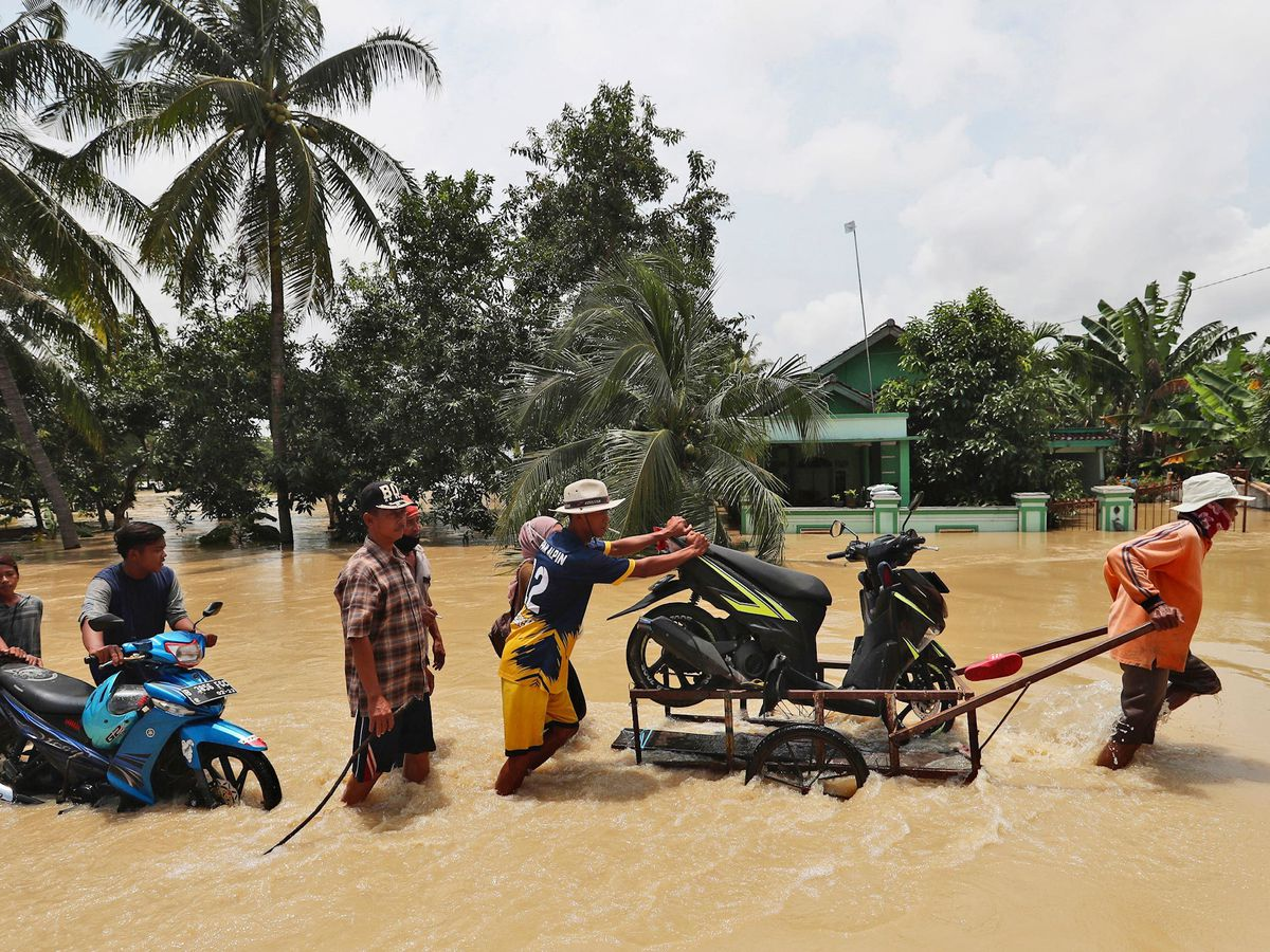 People push belongings through a flooded area in Indonesia