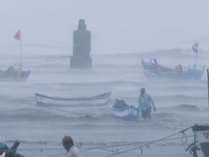 A fisherman waits for help as he tries to move a boat to safer ground