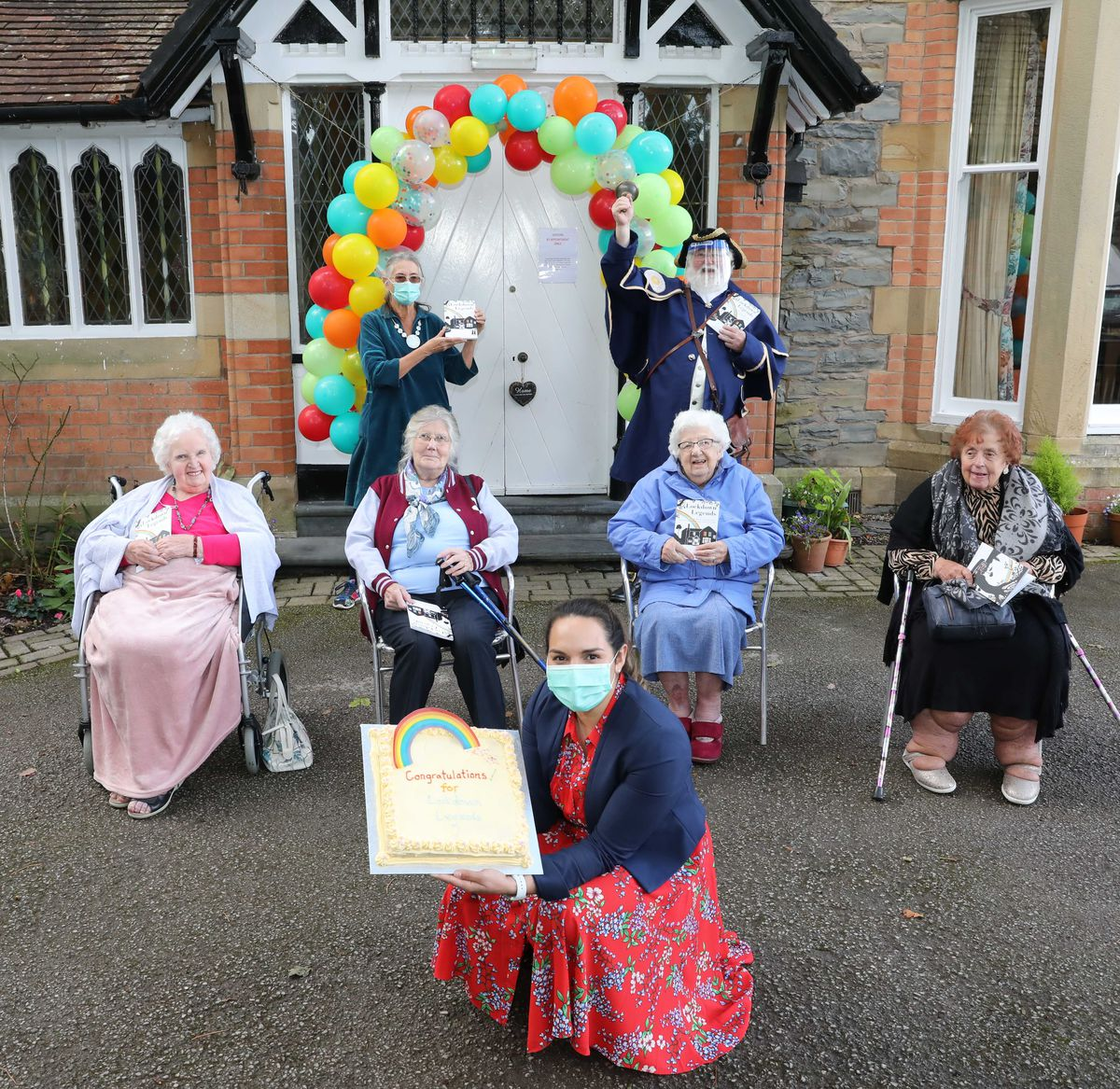 Pictured at the back are storyteller Fiona Collins and Town Crier  Austin 'Chem' Cheminais  with  Joan Fell 96, Jill Lidgit 85, Ena Strange 99, and Yola Roberts 87 and owner Bethan Mascarenhas with the celebration cake