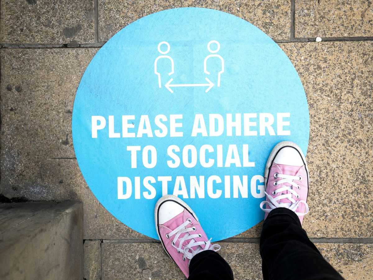 A social distancing sign outside a shop