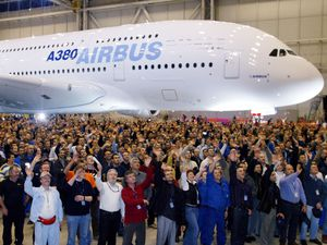 Airbus employees wave as they pose for a family photo in front of 555-seat super jumbo Airbus A380 inaugurated in the Jean-Luc Lagardere final assembly line hall in Toulouse, southern France, January 18, 2005.   REUTERS/Jean-Philippe Arles