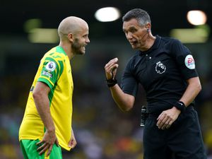"""Norwich City's Teemu Pukki with referee Andre Marriner during the Premier League match at Carrow Road, Norwich. Picture date: Saturday August 14, 2021. PA Photo. See PA story SOCCER Norwich. Photo credit should read: Joe Giddens/PA Wire.   RESTRICTIONS: EDITORIAL USE ONLY No use with unauthorised  audio, video, data, fixture lists, club/league logos or """"live"""" services. Online in-match use limited to 120 images, no video emulation. No use in betting, games or single club/league/player publications."""