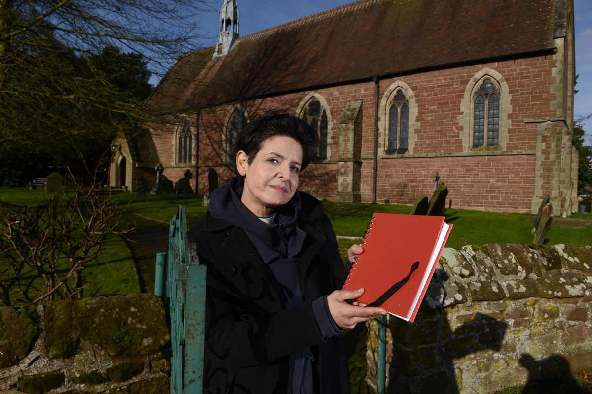 Vicar of St Andrew's Church, Zoe Heming, with a book where people can write down their thoughts and feelings over the tragedy