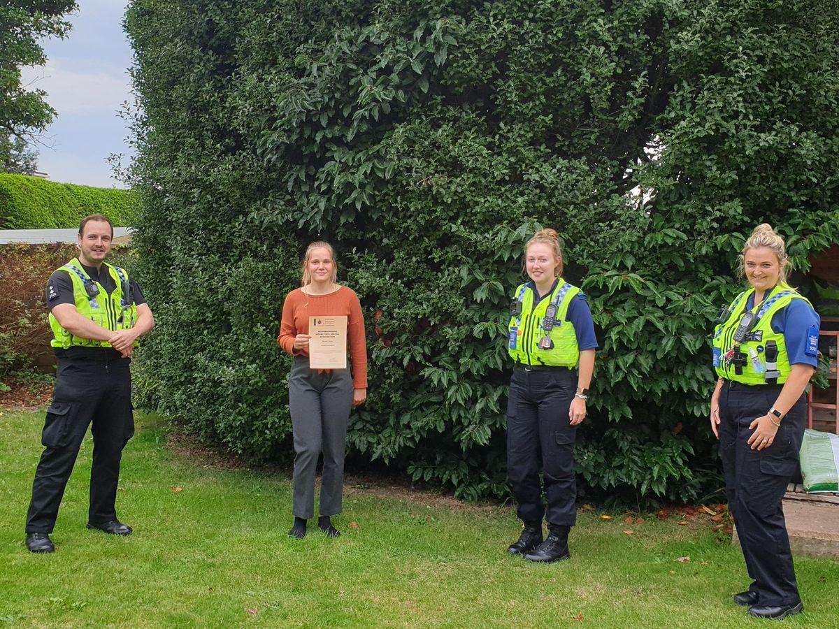 Naomi Jupp receives her award from Dorset Police neighbourhood officers (Dorset Police/PA)