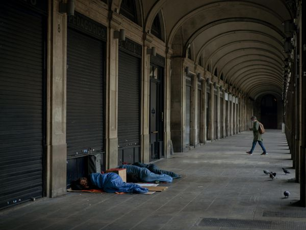 Homeless people sleep on a square where restaurants are closed due to sharpest resurgences of coronavirus in Barcelona, Spain (Emilio Morenatti/AP)