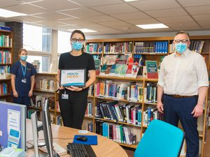 Kenna Blackburn, Outreach Librarian, being presented with the Health Hero Award by Mark Brandreth, Chief Executive, alongside Elaine Richardson, Acute Pain Sister