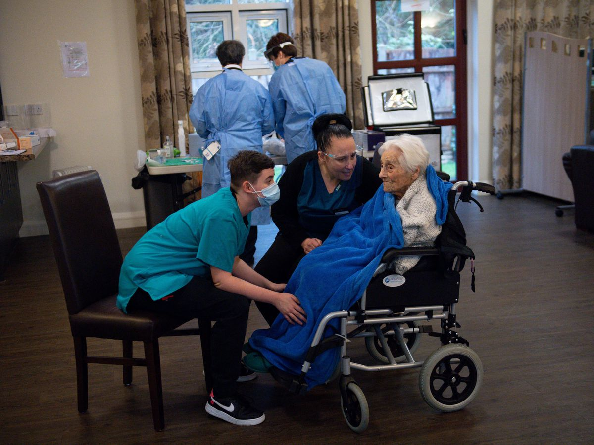 Care home workers comfort a resident