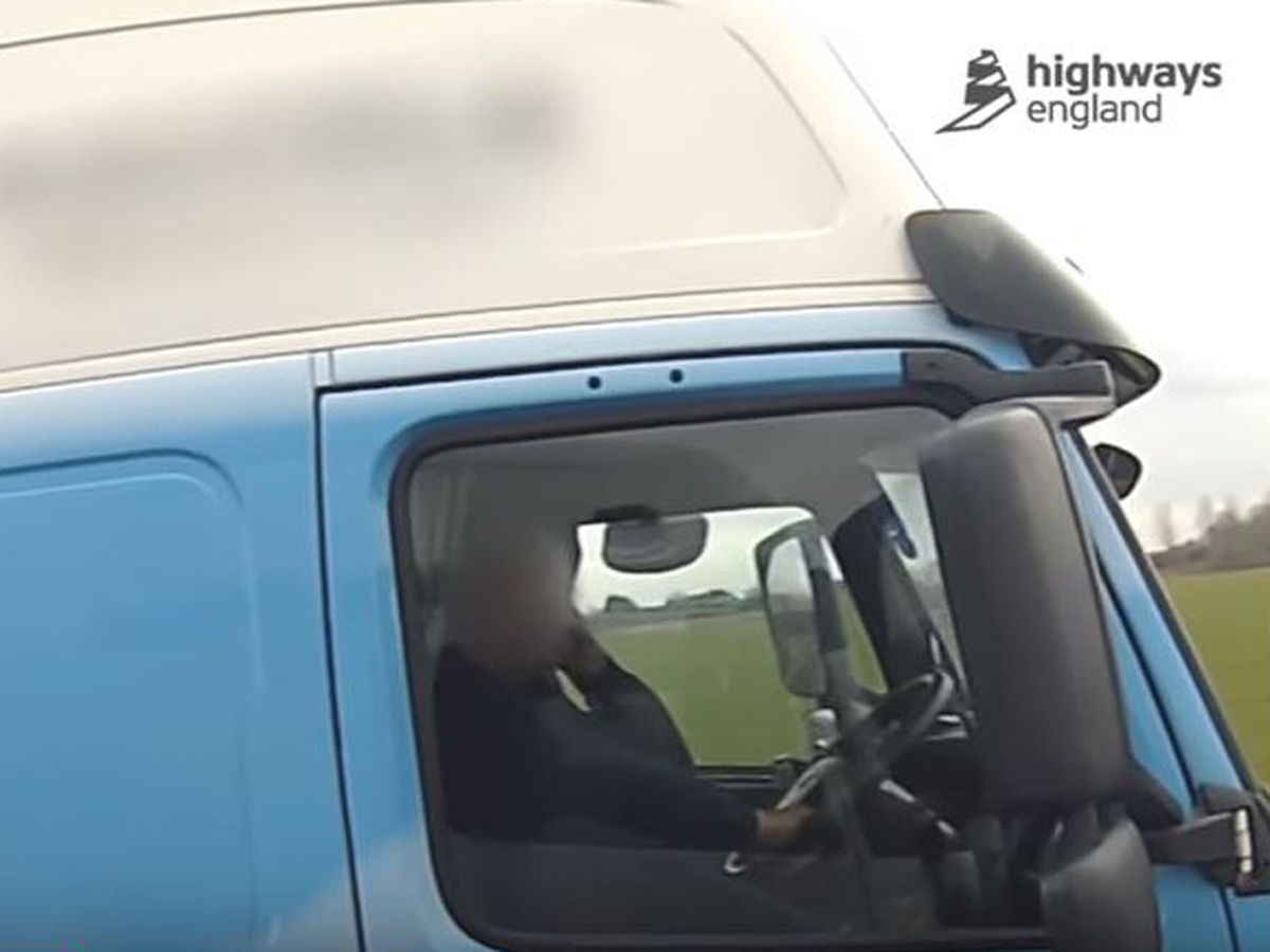 A trucker checks his phone while his right foot is on the dashboard