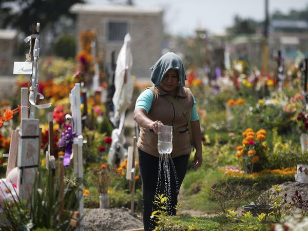 A woman waters her father's grave at the Valle de Chalco municipal cemetery on the outskirts of Mexico City (Fernando Llano/AP)
