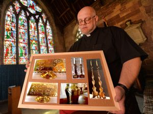 The Rev Gary Ward from All Saints Church with a board showing the stolen items