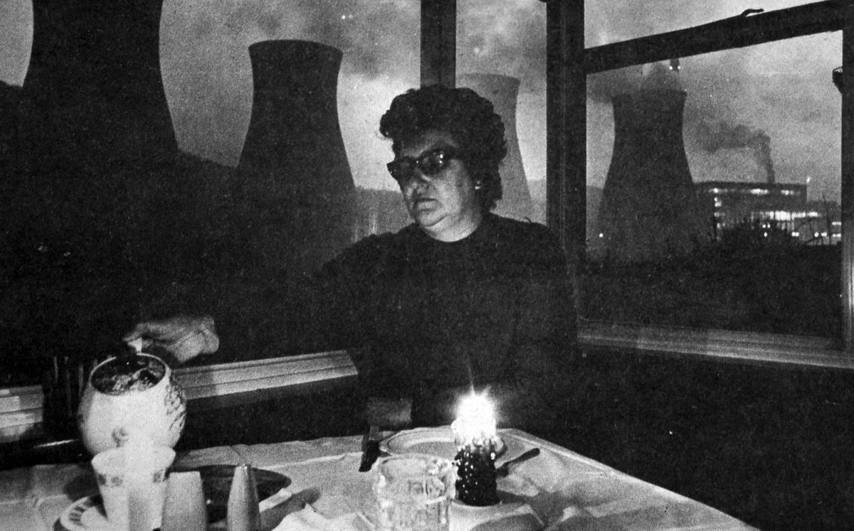 Householder Mrs Jean Prince pours a cup of tea by candlelight during a December 1970 power cut. In the background, with lights blazing, is Ironbridge Power Station.